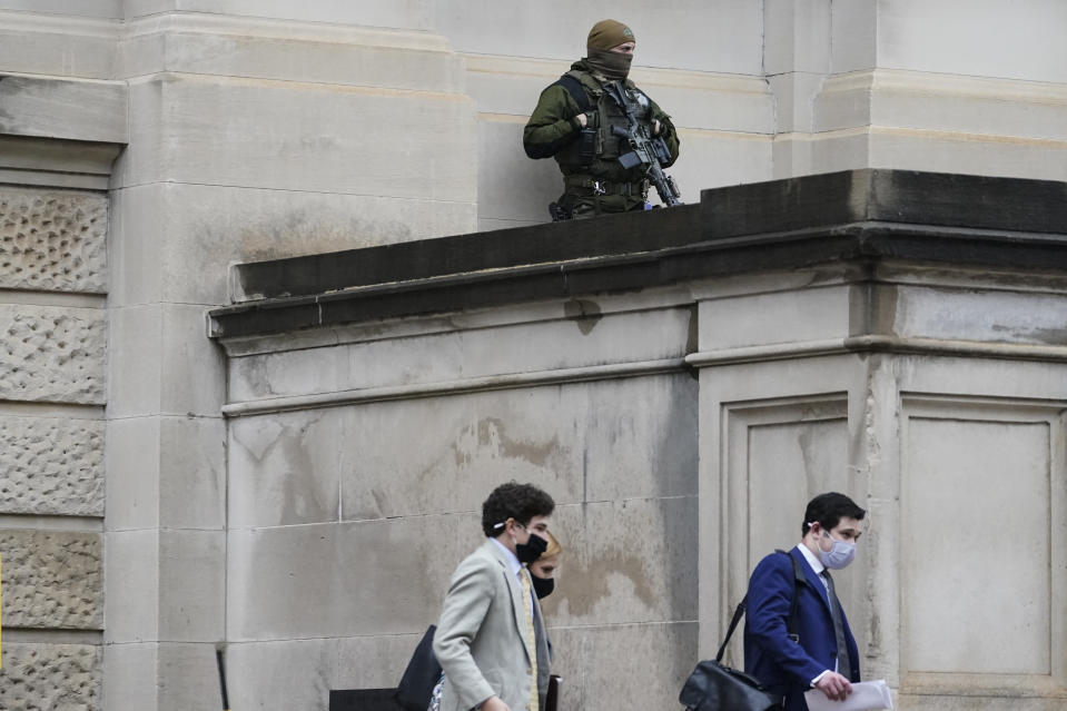 A member of the Georgia State Patrol SWAT team looks on as people walk by outside of the Georgia State capitol after the opening day of the legislative session on Monday, Jan. 11, 2021, in Atlanta. State capitols across the country are under heightened security after the siege of the U.S. Capitol last week. (AP Photo/Brynn Anderson)