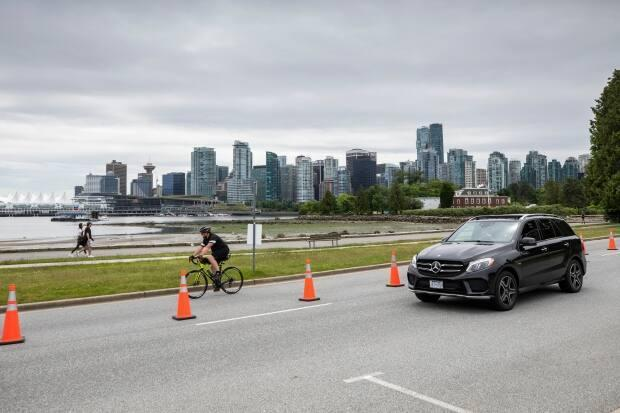 A cyclist and motorist cruise along Stanley Park Drive on June 22, 2020. (Ben Nelms/CBC - image credit)