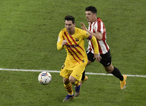 Barcelona's Lionel Messi runs with the ball during the Spanish La Liga soccer match between Athletic Bilbao and Barcelona at San Mames stadium in Bilbao, Spain, Wednesday, Jan. 6, 2021.(AP Photo/Alvaro Barrientos)