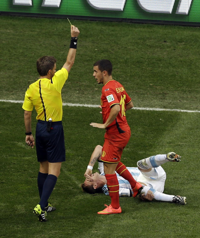 Referee Nicola Rizzoli from Italy issues a yellow card to Belgium's Eden Hazard for a foul against Argentina's Lucas Biglia, bottom during the World Cup quarterfinal soccer match between Argentina and Belgium at the Estadio Nacional in Brasilia, Brazil, Saturday, July 5, 2014. (AP Photo/Thanassis Stavrakis)