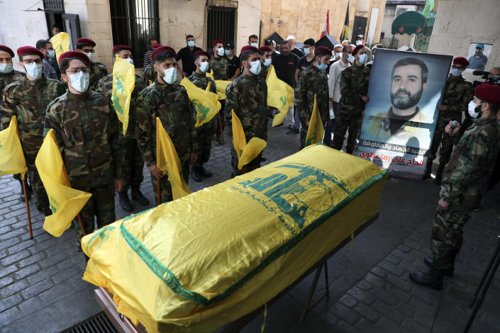 Hezbollah fighters stand in front of the coffin of Ali Atwa, a senior Hezbollah operative, during his funeral procession in the southern Beirut suburb of Dahiyeh, Lebanon, Saturday, Oct. 9, 2021. Atwa was placed on the FBI's most wanted list in 2001, with two other alleged participants in the 1985 hijacking of TWA Flight 847, one of the worst hijackings in aviation history and that lasted for 16 days. (AP Photo/Bilal Hussein)