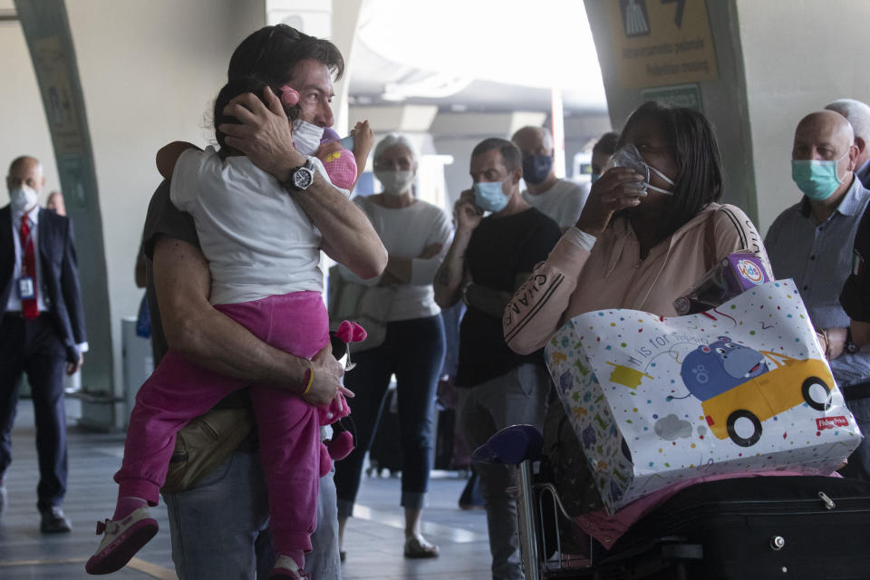 Sandro Manzato, from the Veneto region, hugs his daughter Yearline, 3, as she arrives with her mum Rubiela Perea, right, from Bogota, Colombia, at Rome's Fiumicino airport, Wednesday, June 3, 2020. Rome's Fiumicino airport sprang back to life on Wednesday as Italy opened regional and international borders in the final phase of easing its long coronavirus lockdown, allowing families and loved ones separated by the global pandemic to finally reunite. (AP Photo/Alessandra Tarantino)