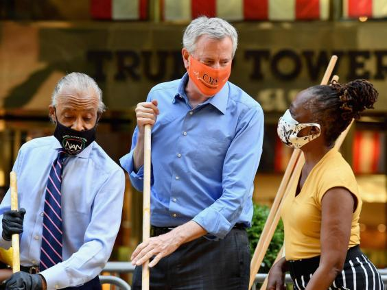 The Reverend Al Sharpton, New York Mayor Bill de Blasio and his wife Chirlane McCray, paint a new Black Lives Matter mural outside of Trump Tower (AFP via Getty Images)