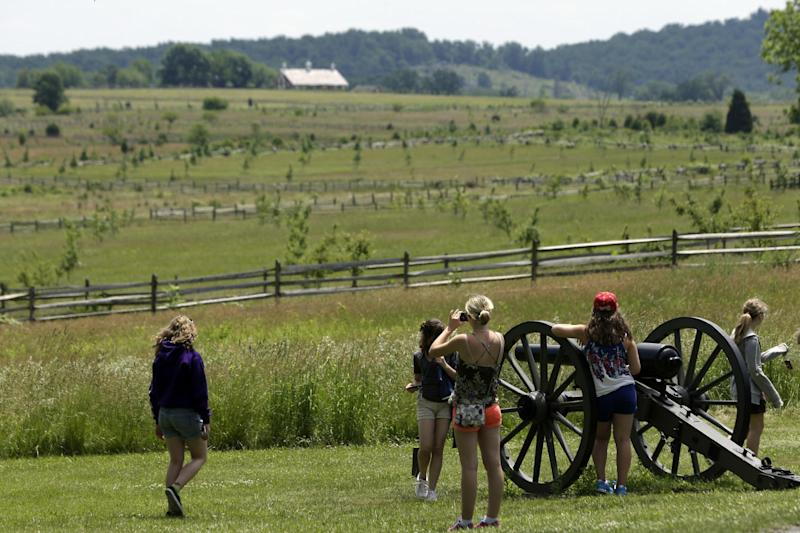 In this June 5, 2013 file photo tourist gather near a Confederate artillery piece that sit atop a ridge above the field of Pickett's Charge, in Gettysburg, Pa. As the 150th anniversary of the Battle of Gettysburg draws near the character and historic legacy of the town remain divided as hundreds of thousands of tourists visit the battlefield where so many died and development continues unabated around the site, drawing outlet shopping, restaurants and a casino. (AP Photo/Matt Rourke, File)