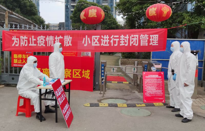 Workers in protective suits are seen at a checkpoint for registration and body temperature measurement, at an entrance to a residential compound in Wuhan