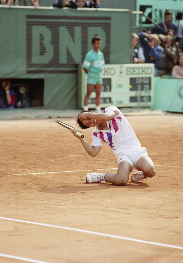 FILE - In this June 5, 1989, file photo, Michael Chang falls to the ground crying after he defeated top-seeded Ivan Lendl at the French Open tennis championships in Paris. Chang, 17, toppled the top-seeded Lendl 4-6, 4-6, 6-3, 6-3, 6-3. (AP Photo/Lionel Cironneau, File)