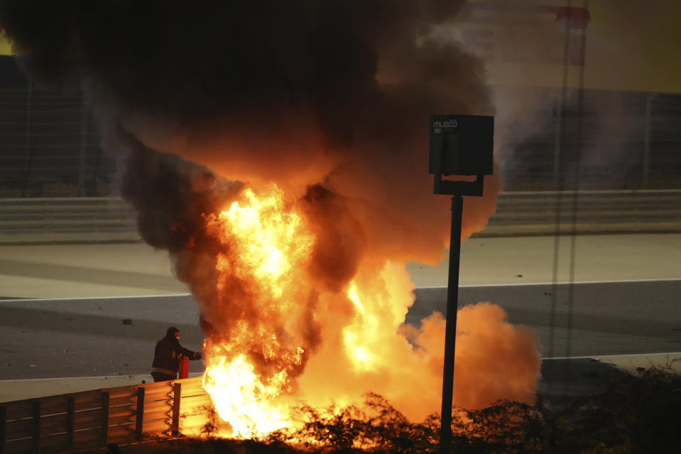 Staff extinguish flames from Haas driver Romain Grosjean of France's car after a crash during the Formula One race in Bahrain International Circuit in Sakhir, Bahrain, Sunday, Nov. 29, 2020. (Brynn Lennon, Pool via AP)