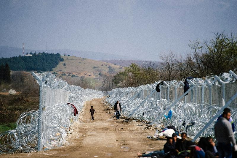 Migrants and refugees walk past a barbed wire fence at the Greek-Macedonian border near Gevgelija, on March 1, 2016 (AFP Photo/Dimitar Dilkoff)