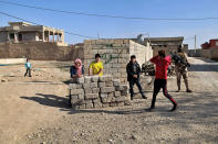 Local Yazidis stand outside their homes in the village of Tal Binat, Sinjar, Iraq, Friday, Dec. 4, 2020. A new agreement aims to bring order to Iraq's northern region of Sinjar, home to the Yazidi religious minority brutalized by the Islamic State group. Since IS's fall, a tangled web of militia forces have run the area, near the Syrian border. Now their flags are coming down, and the Iraqi military has deployed in Sinjar for the first time in nearly 20 years. (AP Photo/Samya Kullab).