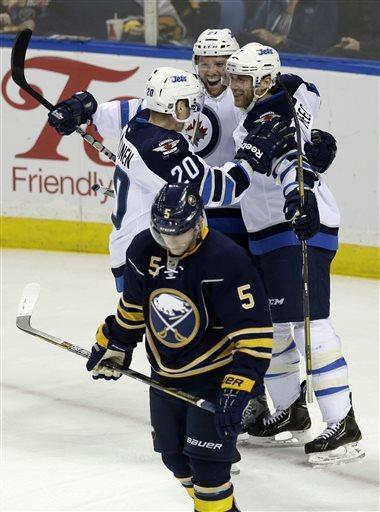 Buffalo Sabres' Chad Ruhwedel (5) skates away as Winnipeg Jets' Aaron Gagnon (21) celebrates his goal with Antti Miettinen (20) and Derek Meech (7) during the second period of an NHL hockey game in Buffalo, N.Y., Monday, April 22, 2013. (AP Photo/David Duprey)