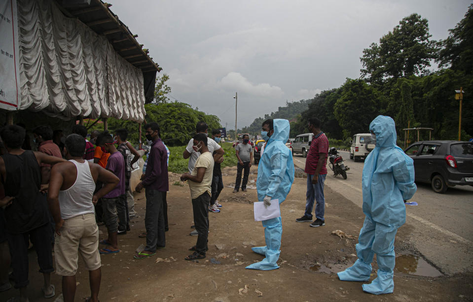 Health workers in protective gear stand in queue with others to get entry passes to travel back to neighboring Meghalaya state as they return after bringing a COVID-19 patient in Gauhati, India, Sunday, Aug. 9, 2020. Interstate travel is restricted due to the pandemic. (AP Photo/Anupam Nath)