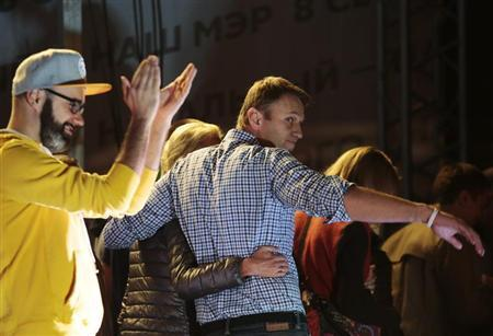 Russian opposition leader Alexei Navalny and his wife Yulia leave the stage during a rally in Moscow