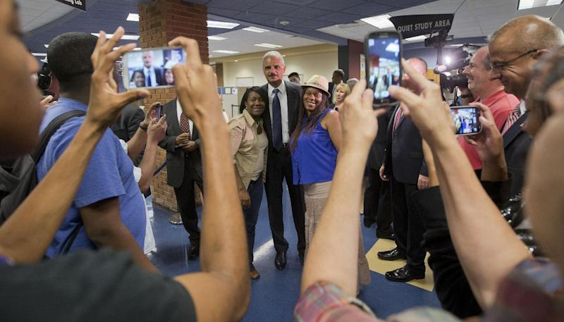 Attorney General Eric Holder (C) poses for photographs following his meeting with students at St. Louis Community College Florissant Valley, on August 20, 2014 in Ferguson, Missouri (AFP Photo/Pablo Martinez Monsivais)