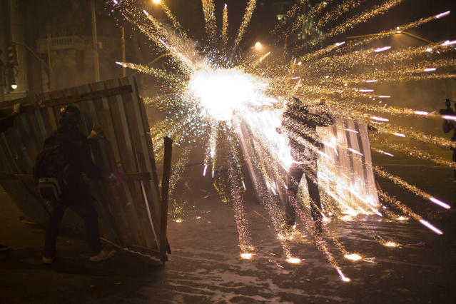 AP10ThingsToSee - A burst of fireworks go off near members of the so-called Black Bloc anarchist group during clashes with police after a march of striking teachers took place to mark National Teachers Day, in Rio de Janeiro, Brazil, Tuesday, Oct. 15, 2013. Last week, a largely peaceful rally of teachers turned violent in Rio when small groups of masked protesters started hurling rocks and gasoline bombs and set fire to a passenger bus. Black Bloc anarchists, who earlier joined in the march with teachers, tried to incite the crowd Tuesday but were kept in check by other demonstrators. (AP Photo/Felipe Dana, File)