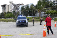 Florida Fish and Wildlife Conservation Commission officials stand outside of a 12-story beachfront condo building which partially collapsed, Friday, June 25, 2021, in the Surfside area of Miami. The apartment building partially collapsed on Thursday. (AP Photo/Lynne Sladky)