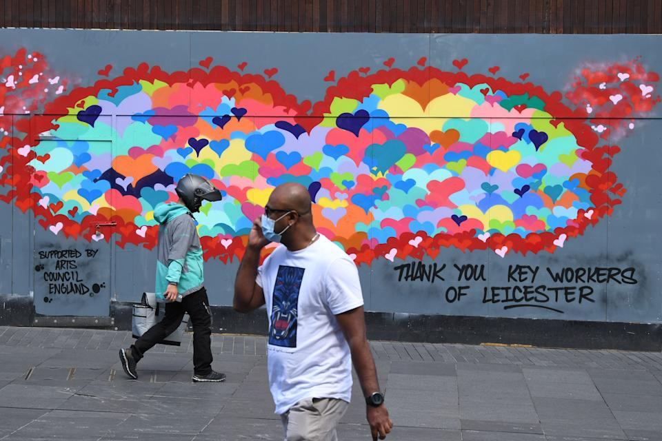 """A man wearing a face mask as a precaution against the transmission of the novel coronavirus and a devliery worker walk past a piece of street art thanking key workers for their efforts during the pandemic in the centre of Leicester, central England on July 17, 2020, as local lockdown restrictions remain in force due to a spike in cases of the novel coronavirus in the city. - Boris Johnson said on July 17 he hoped Britain would """"return to normality"""" by November despite being badly affected by the coronavirus and predictions of a second wave of cases during winter months. The prime minister announced fresh powers for councils to impose  local lockdowns, such as one currently in place in the English midlands city of Leicester, if there were increased number of cases elsewhere. The government on July 16 annouced a partially ease a two-week-old local lockdown in Leicester, after the number of new coronavirus cases had fallen, but remained well above the average for England which means restrictions on schools, early years childcare and non-essential retail stores will be relaxed from July 24, but that other measures impacting travel, social gatherings and the hospitality sector would remain. (Photo by DANIEL LEAL-OLIVAS / AFP) (Photo by DANIEL LEAL-OLIVAS/AFP via Getty Images)"""