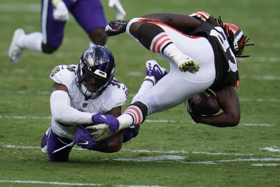 Baltimore Ravens safety Chuck Clark (36) grabs Cleveland Browns running back Kareem Hunt's (27) foot, during the second half of an NFL football game, Sunday, Sept. 13, 2020, in Baltimore, MD. (AP Photo/Julio Cortez)