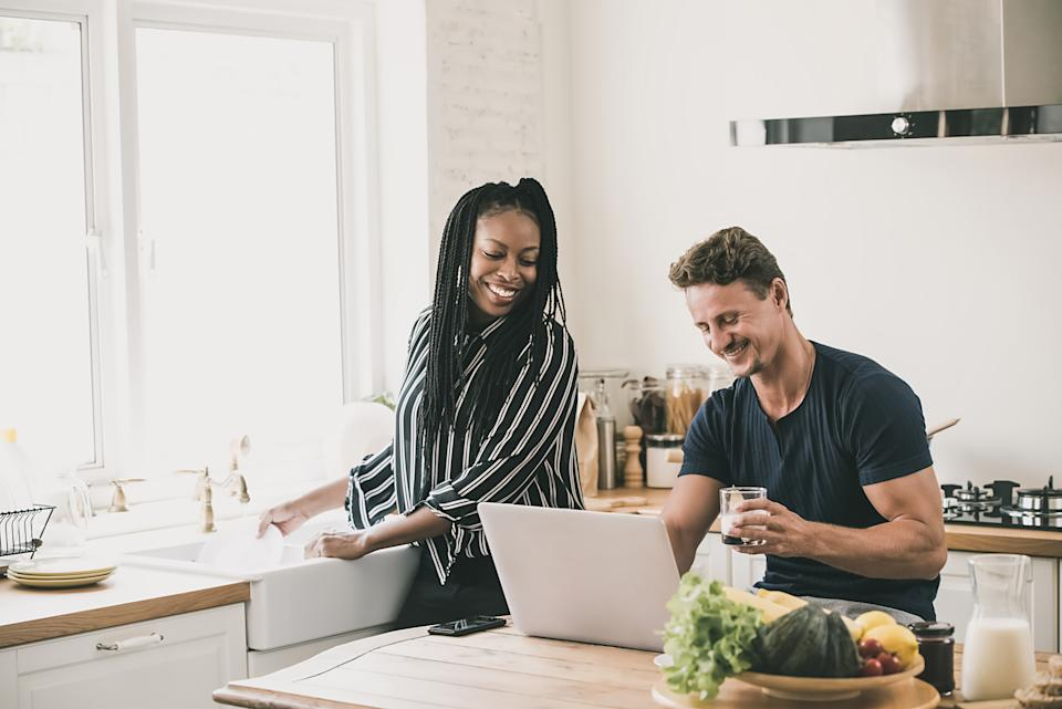 Happy married interracial couple looking at laptop computer together while doing daily moring routines in the kitchen at home