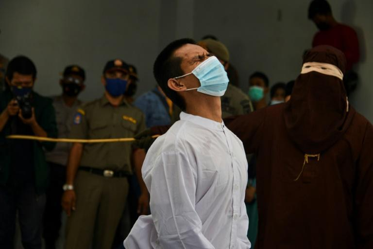 A man accused of having gay sex is publicly caned by a member of the Sharia police in Banda Aceh on January 28