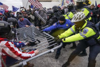 FILE - In this Jan. 6, 2021, file photo violent insurrectionists loyal to President Donald Trump hold on to a police barrier at the Capitol in Washington. Months after Donald Trump's supporters besieged the Capitol, the ex-president and his supporters are revising their account of that day. (AP Photo/John Minchillo, File)