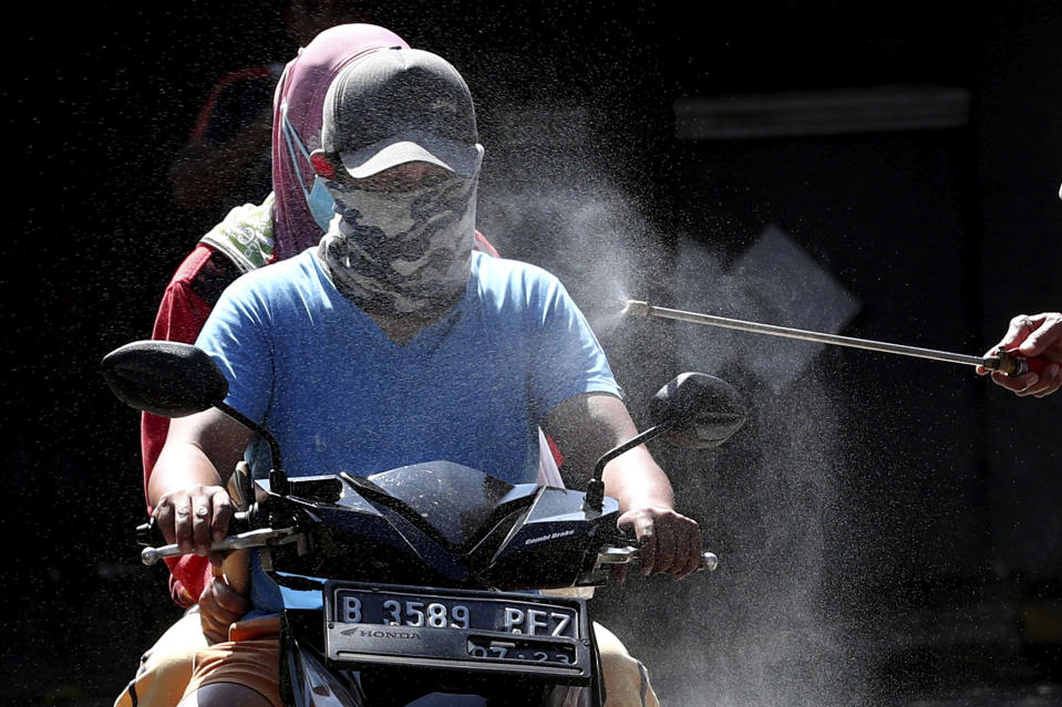 Motorists are sprayed with disinfectant in an attempt to curb the spread of coronavirus outbreak at the gate of a housing complex in South Tangerang, Indonesia, Tuesday, March 31, 2020. Indonesia will close its doors to foreign arrivals in an attempt to curb the coronavirus spread while the country plans to bring home more than a million nationals working abroad. (AP Photo/Tatan Syuflana)