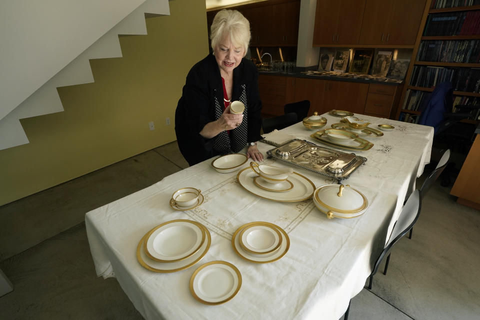 """Diane Capone looks over one of the pieces of a china set that once belonged to her grandparents, Mae and Al Capone, on display at Witherell's Auction House in Sacramento, Calif., Wednesday, Aug. 25, 2021. The granddaughter of the famous mob boss and her two surviving sisters will sell 174 family heirlooms at an Oct. 8 auction titled """"A Century of Notoriety: The Estate of Al Capone, that will be held by Witherell's in Sacramento. (AP Photo/Rich Pedroncelli)"""
