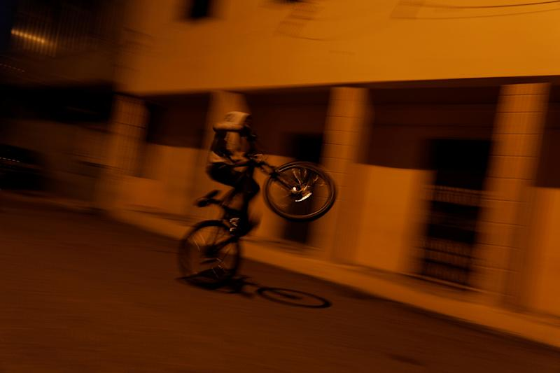 A boy rides a bicycle on a street in Cova da Moura