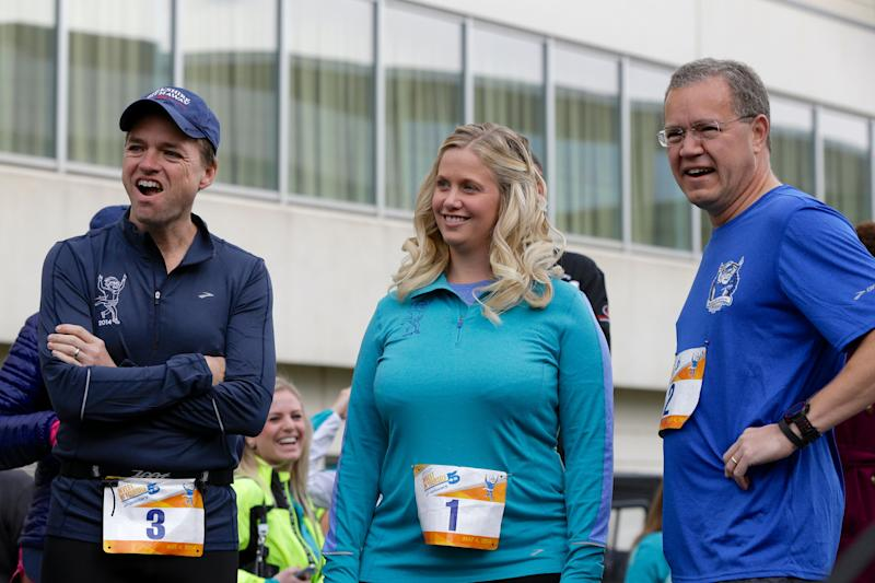 Berkshire Hathaway investment managers Todd Combs, left, Ted Weschler, right, and Tracy Britt Cool, Chairman of Berkshire companies Benjamin Moore, Johns Manville, Oriental Trading Company and Larson-Juhl, center, prepare to launch a 5K run sponsored by the Brooks Running Company. (AP Photo/Nati Harnik)