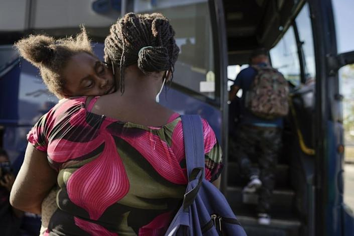 A child sleeps on the shoulder of a woman as they prepare to board a bus to San Antonio moments after a group of migrants, many from Haiti, were released from custody upon crossing the Texas-Mexico border in search of asylum, Wednesday, Sept. 22, 2021, in Del Rio, Texas. (AP Photo/Julio Cortez)