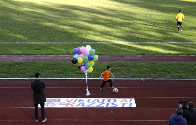 A boy runs past a banner reading in Italian ' Forbidden to racists ', prior to a youth team soccer match between Desio and Sovicese, at the municipal stadium in Desio, near Milan, Italy, Saturday, Nov. 9, 2019. The initiative comes a week after an Aurora Desio team's 10-year-old player was allegedly subjected to racist abuse during a match. (AP Photo/Luca Bruno)