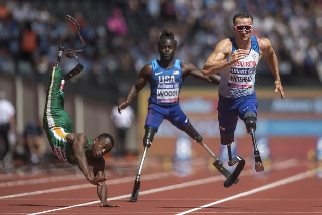 South Africa's Ntando Mahlangu takes a dramatic tumble during the 2017 World Para Athletics Championships at London Stadium. Great Britain's Richard Whitehead, right, went on to win the men's 100m T42 first heat during day four of the competition (Victoria Jones/PA)