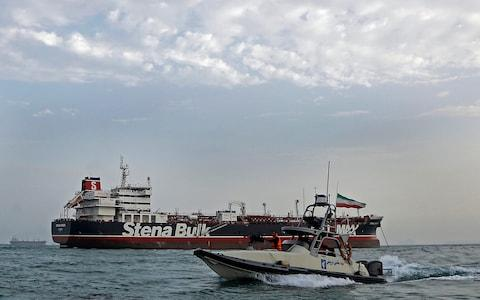 A speedboat of the Iran's Revolutionary Guard moves around a British-flagged oil tanker Stena Impero, which was seized on Friday by the Guard, in the Iranian port of Bandar Abbas, - Credit: AP