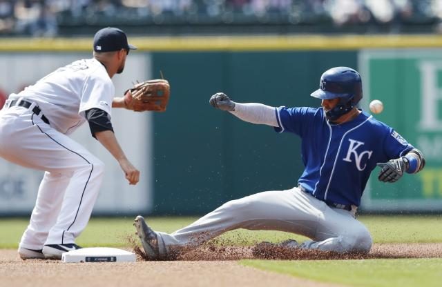 Kansas City Royals' Whit Merrifield, right, safely beats the throw to Detroit Tigers shortstop Jordy Mercer for a double during the first inning of a baseball game, Sunday, April 7, 2019, in Detroit. (AP Photo/Carlos Osorio)