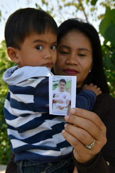 """Alma Tome, accompanied by her son, shows a photo of her husband -- her son still calls out """"papa"""" when a car stops in front of their house"""