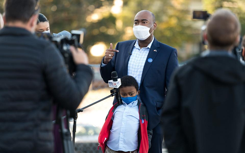 Democratic US senate candidate Jaime Harrison, with his son, William, after casting his vote - Getty