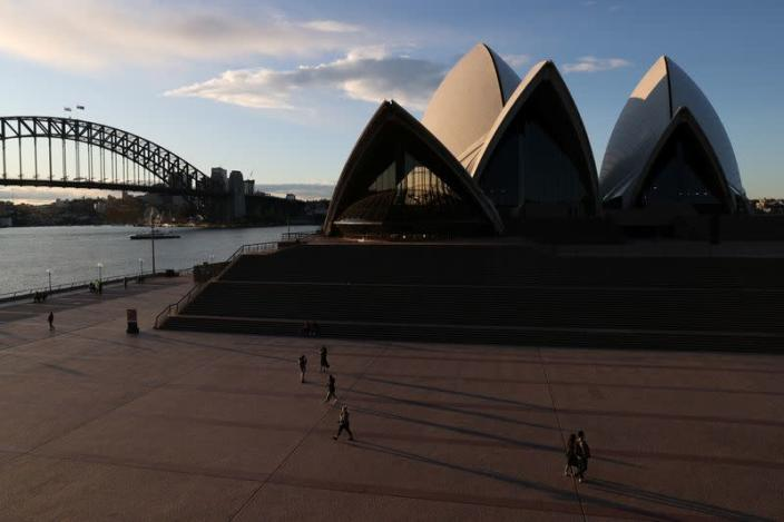 People are seen walking in front of the Sydney Opera House and Sydney Harbour Bridge in Sydney