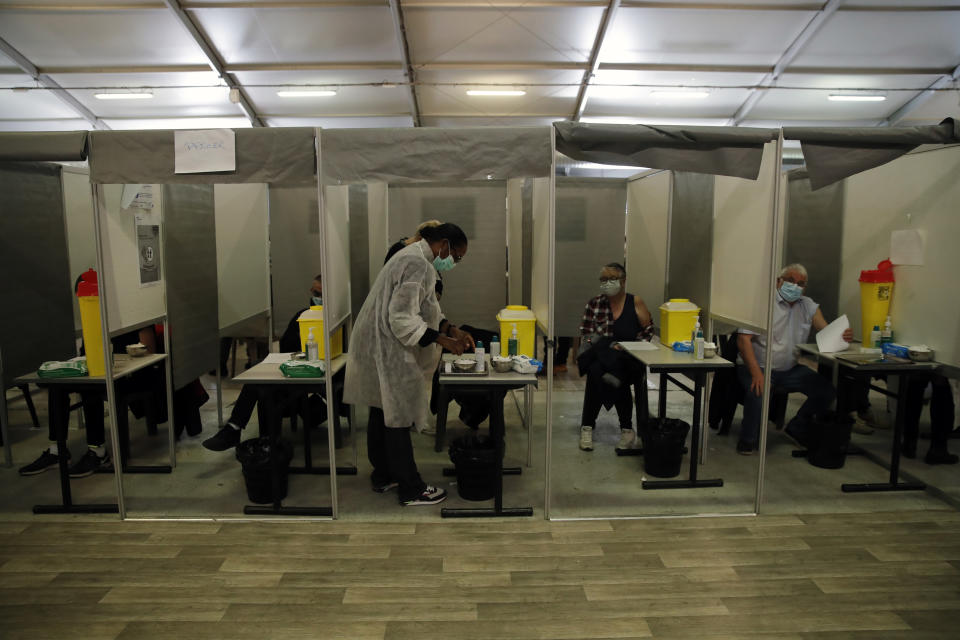 Patients receive Pfizer and Moderna's COVID-19 vaccine in a vaccination site in Sarcelles, outside Paris, Sunday, April 4, 2021. Some 9,000 people are getting vaccinated at a huge stadium in Lyon during Easter weekend, and thousands more around France are spending the holiday lining up for injections elsewhere as the government tries to speed up vaccinations amid a new virus surge. (AP Photo/Christophe Ena)