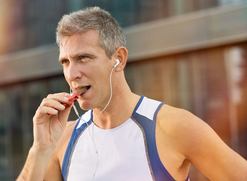 Older male runner eating protein bar
