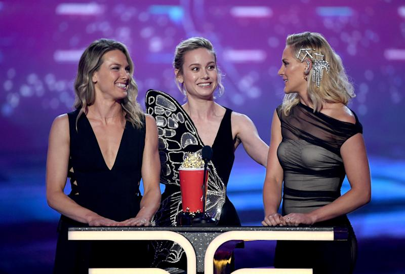SANTA MONICA, CALIFORNIA - JUNE 15: (L-R) Brie Larson and stunt doubles Ingrid Kleinig and Joanna Bennett accept the Best Fight award for 'Captain Marvel' onstage during the 2019 MTV Movie and TV Awards at Barker Hangar on June 15, 2019 in Santa Monica, California. (Photo by Kevin Winter/Getty Images for MTV)