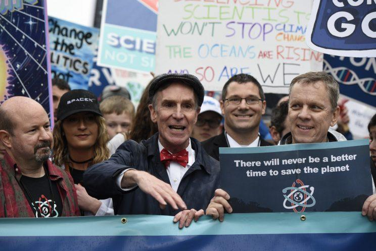 Bill Nye surrounded by people holding signs at the March for Science
