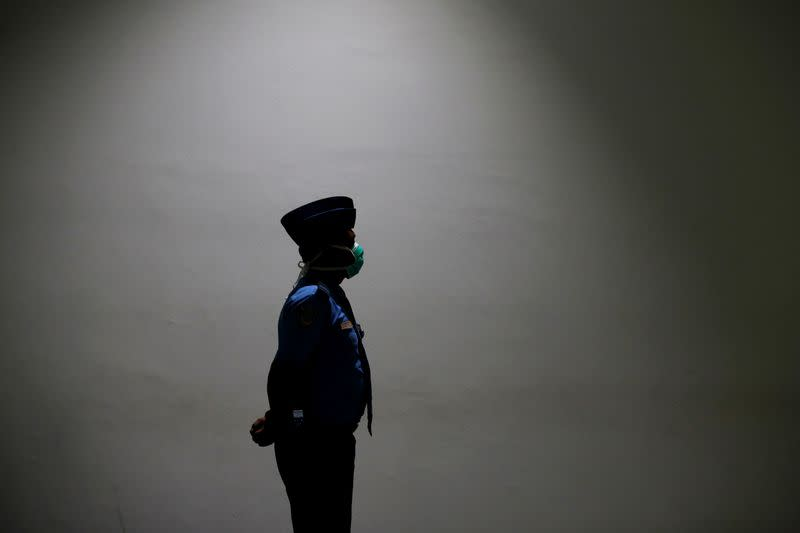 An aviation security officer wearing medical mask stands as he guards at international arrival terminal of Soekarno Hatta airport near Jakarta