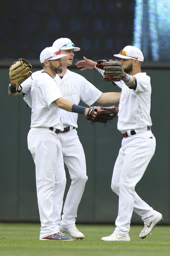 Minnesota Twins' Jake Cave, left, Max Kepler, center, and Marwin Gonzalez, right, celebrate on the field after their 7-4 win against the Detroit Tigers during a baseball game Sunday, Aug. 25, 2019, in Minneapolis. (AP Photo/Stacy Bengs)