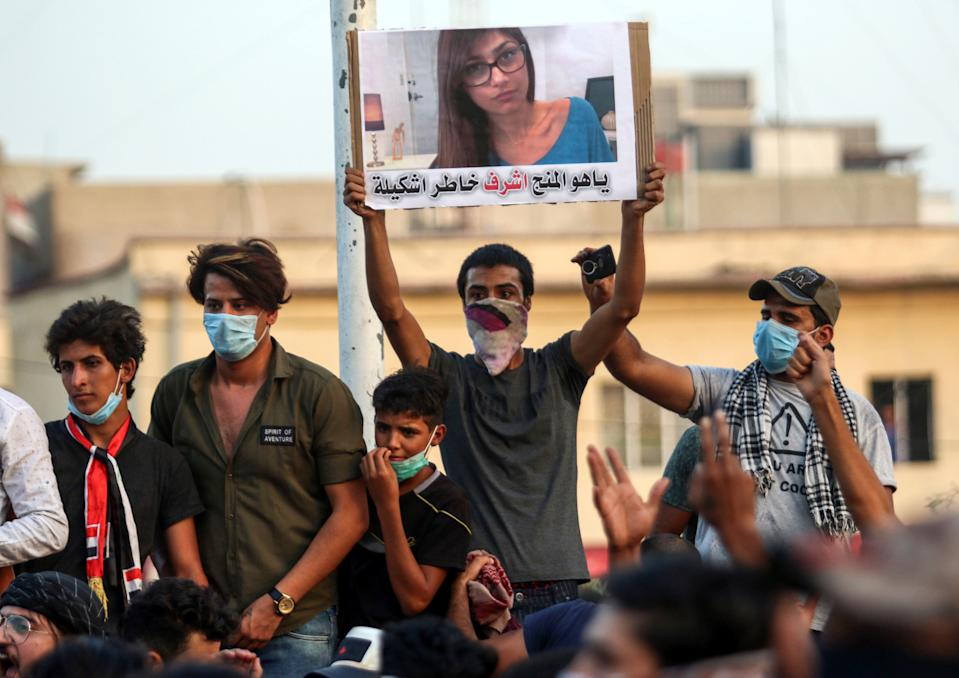 """Iraqi protesters raise a sign bearing the image of Lebanese American pornstar Mia Khalifa, with a caption below reading in Iraqi vernacular Arabic """"who's more honourable than you to complain to"""", as they gather in a demonstration against corruption and lack of basic services outside the local government headquarters in the southern city of Basra on September 2, 2018. (Credit: HAIDAR MOHAMMED ALI/AFP/Getty Images)"""