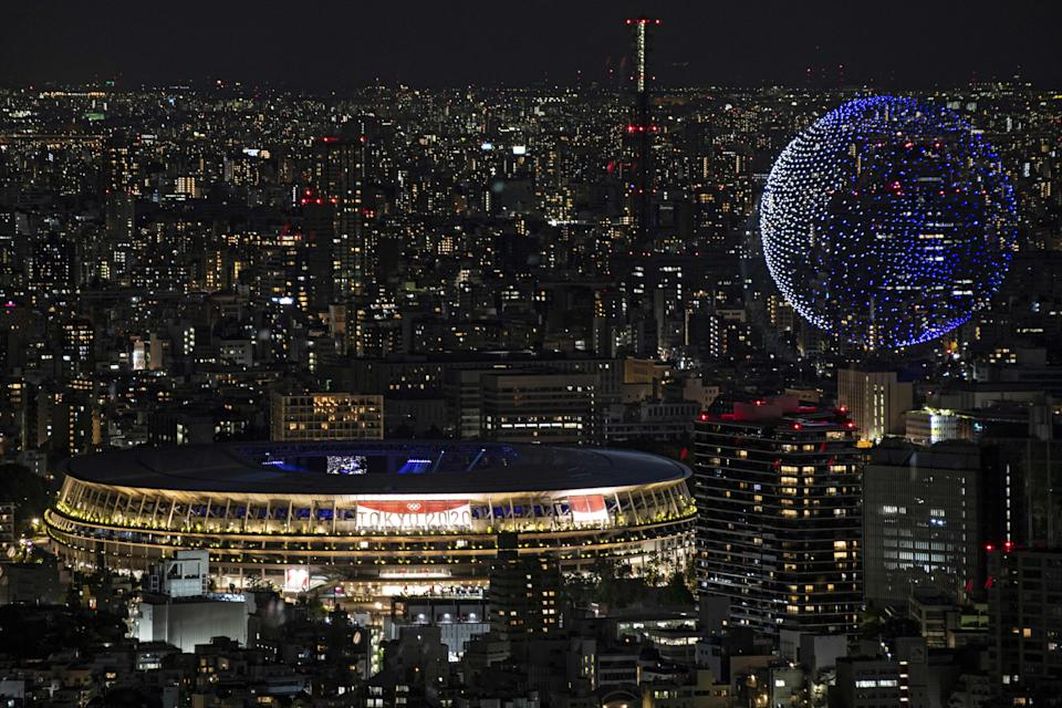 TOPSHOT - Drones fly to form an image of the Earth in the sky over the Olympic Stadium during the opening ceremony of the Tokyo 2020 Olympic Games, in Tokyo, on July 23, 2021. (Photo by Charly TRIBALLEAU / AFP) (Photo by CHARLY TRIBALLEAU/AFP via Getty Images)