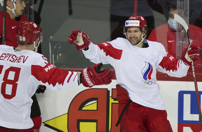 Sergei Tolchinski, right, and Anton Slepyshev of Russia celebrate during the Ice Hockey World Championship group A match between the Switzerland and Russia at the Olympic Sports Center in Riga, Latvia, Saturday, May 29, 2021. (AP Photo/Roman Koksarov)