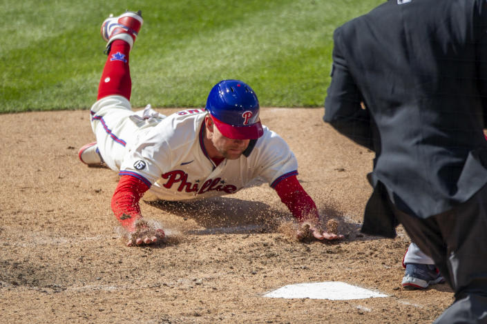 Philadelphia Phillies first baseman Rhys Hoskins (17) slides into home plate to score on an RBI single by Alec Bohm during the eighth inning of a baseball game against the Atlanta Braves, Sunday, April 4, 2021, in Philadelphia. (AP Photo/Laurence Kesterson)