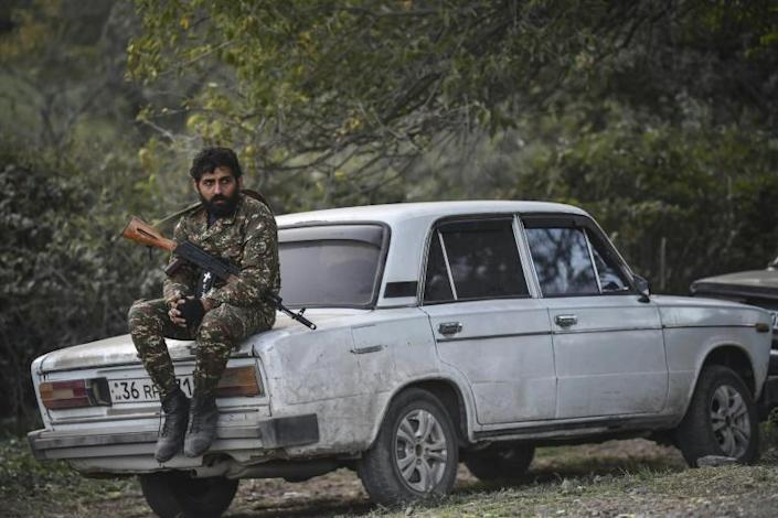 A volunteer fighter sits on a car as cannons fire nearby