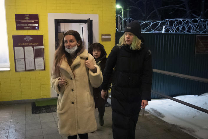 """Eva Sokolova, left, walks out of the deportation centre Sakharovo, 70km (43,7 miles) south-west of Moscow which was urgently transformed into a detention center in the absence of prison space where she has spent 3 days outside Moscow, Russia, Wednesday, Feb. 3, 2021. Eva Sokolova slept two nights on the floor of police precinct before the court jailed her for three days. """"There were four of us in the holding cell who slept on the floor on the mattress with single-use sheets, without pillows and blankets,"""" she said leaving the custody. (AP Photo/Pavel Golovkin)"""