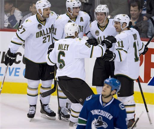 Dallas Stars right wing Reilly Smith (18) celebrates his goal as Vancouver Canucks defenseman Kevin Bieksa (3) skates past during the first period of an NHL hockey game in Vancouver, British Columbia, Friday, Feb. 15, 2013. (AP Photo/The Canadian Press, Jonathan Hayward)