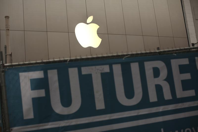The Apple logo is pictured on the front of the company's flagship retail store near signs for the central subway project in San Francisco, California